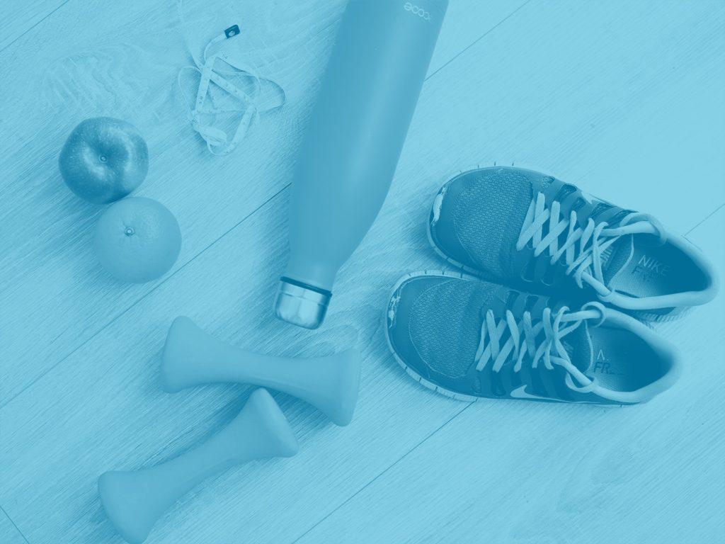 duotone of sneakers, weights, water bottle, apple, headphones